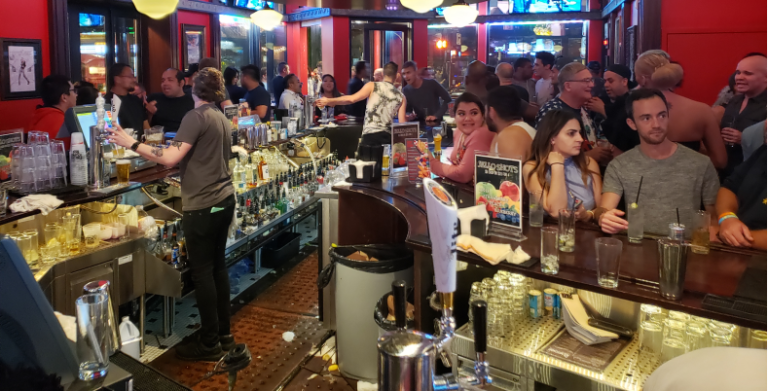 Image of many people crowded around a messy bar
